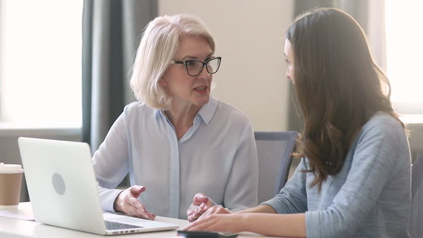 Helpful old female mentor teacher coach teach intern student talk instruct help young trainee with computer work, mature executive manager explain online project to worker learn new skills in office