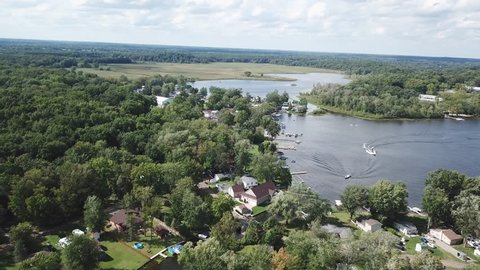 Beautiful sunny summer day on a Michigan chain of lakes. Boating and outdoor fun. Aerial drone footage. Forest surrounding the lakes and rivers.