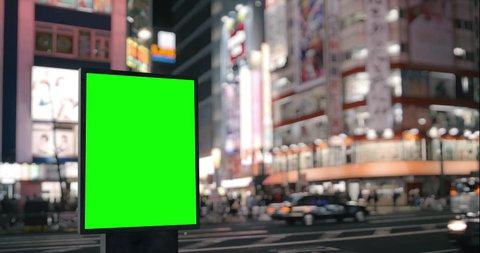 Modern billboard with a green screen, on the blurred megapolis background, neon street lights at night, traffic, Tokyo, Japan
