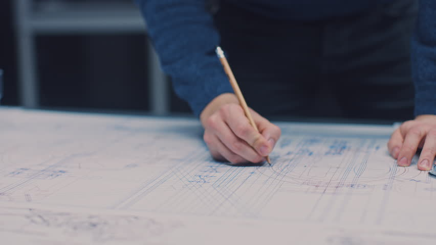 In the Dark Industrial Design Engineering Facility: Male Engineer Works with Blueprints Laying on a Table, Uses Pencil, Ruler and Digital Tablet. On Desktop Multiple Drawings. Focus on Hands