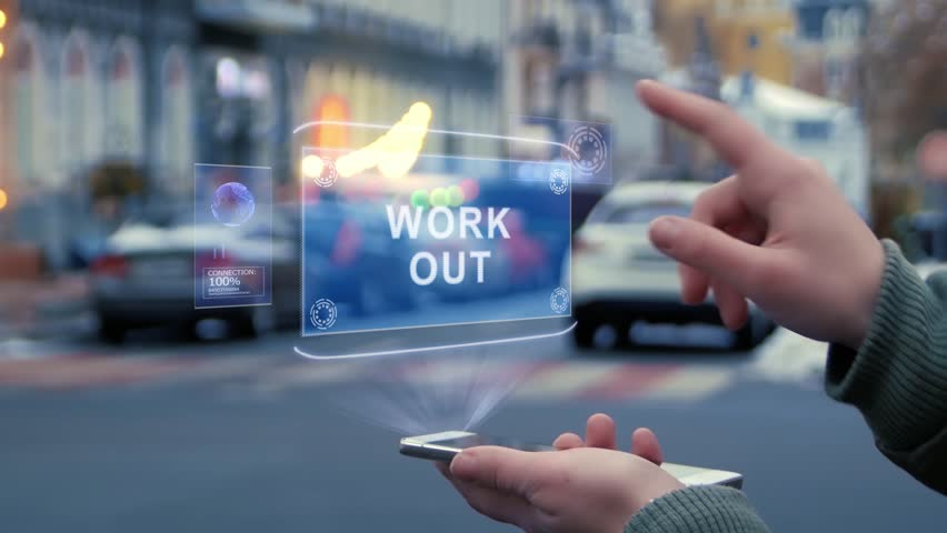 Female hands on street interact with HUD hologram with text Work out. Woman uses the holographic technology of future in smartphone screen on background of evening city | Shutterstock HD Video #1029183719