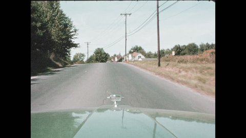 1960s: Tracking shot from car, driving on road, pulling into driveway. View of rock wall.