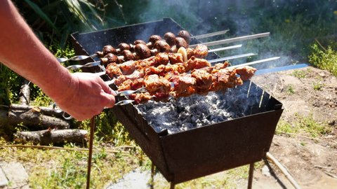 The male hand rotates the skewers with pieces of meat that are roasted on the coals. This is a shish-kebab. Shish-kebab - a popular dish of Caucasian, Turkish and Asian cuisine.