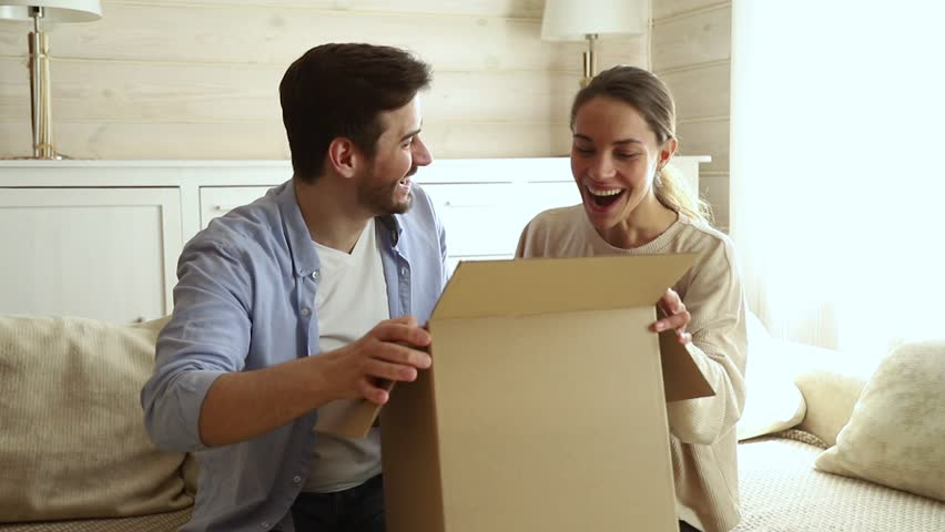 Happy excited couple customers open cardboard box together sit on sofa at home, young family consumers unpack good parcel looking inside receive surprising great purchase delivered by postal shipping