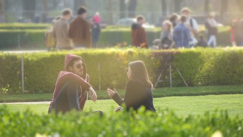 Brussels, Belgium - April 1, 2019: Cheerful view of a young man and a woman sitting, smiling and having a picnic on a green lawn with walking people nearby in Brussels in slo-mo