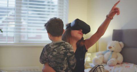 Funny teenager girl with her little brother playing on a bed , at the same time teenager girl playing on a VR