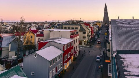 Time lapse of Reykjavik city centrum evening life -moving cars and people on the road. The central street leads to the most famous church - aerial view from above