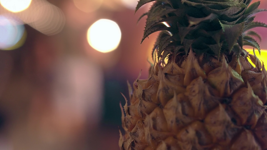 tasty and fresh pineapple with green leaves against bright neon garland people and street market close view
