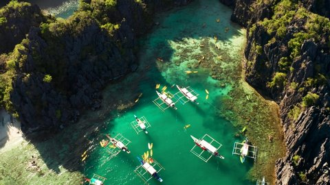 aerial view of tourist boats over tropical lagoon and coral reef. Small lagoon with turquoise water. El nido, Philippines, Palawan. Summer and travel vacation concept.