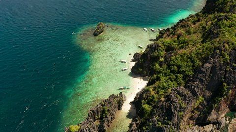Aerial drone tropical landscape bay with beach and clear blue water surrounded by cliffs. El nido, Philippines, Palawan. Seascape with tropical rocky islands, ocean blue water. Summer and travel