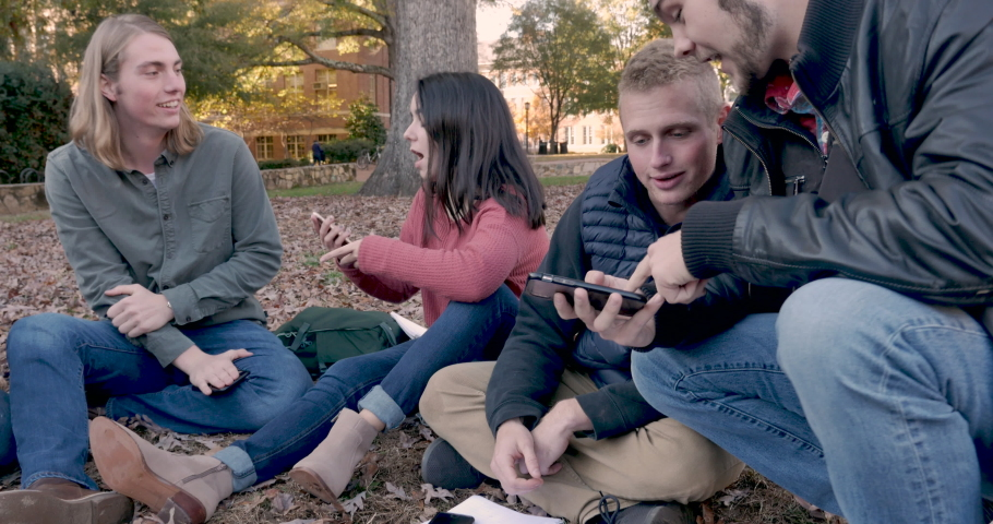 Excited college students sitting outside a college campus showing each other something on their mobile phones such as the newest video game, mobile app, meme, or social media post | Shutterstock HD Video #1029494249