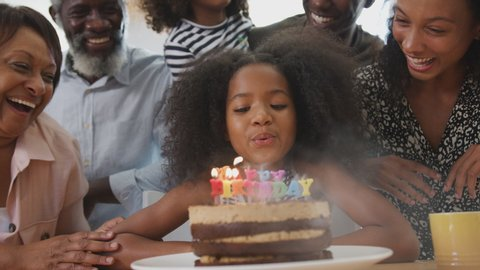 Multi-Generation Family Celebrating Granddaughters Birthday At Home With Cake And Candles