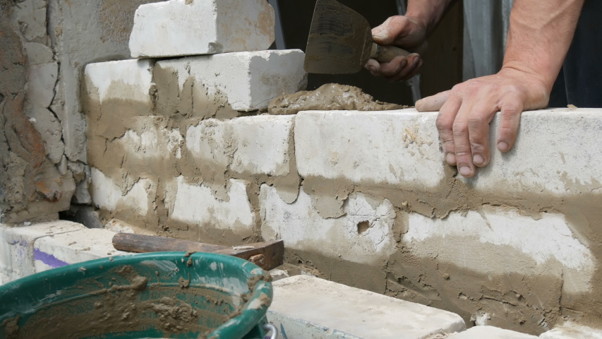 Male builder laying white brick on cement and standing wall. Hands of a man laying building bricks close up view | Shutterstock HD Video #1029554039