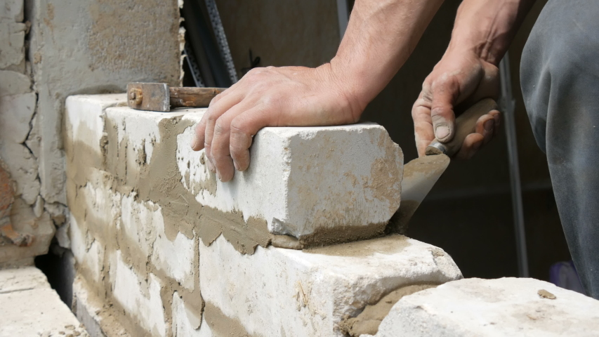 Male builder laying white brick on cement and standing wall. Hands of a man laying building bricks close up view | Shutterstock HD Video #1029554069