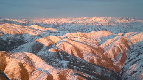 Epic aerial view of the vast mountain ranges of Idaho, as the sun falls to the horizon and skirts over the higher peaks