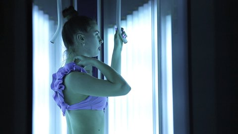 Solarium. Beautiful young girl in a purple swimsuit to tan in the vertical Solarium