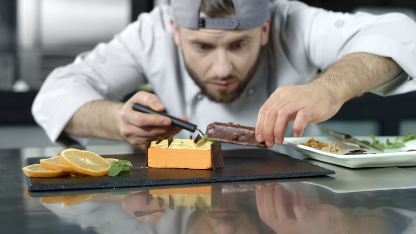 Chef making cake at kitchen workplace. Closeup baker putting dessert in slow motion. Close up professional chef preparing pastry at restaurant kitchen. Male chef cooking chocolate dessert | Shutterstock HD Video #1029702149
