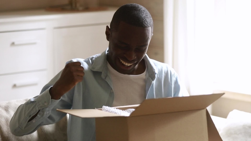 Happy excited african american man customer open parcel cardboard box at home satisfied with good purchase, smiling black male consumer unpack package looking inside received postal shipping delivery