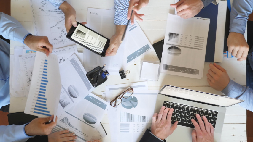 Top view male and female hands of business people planning strategy for corporate project in office. Business team checks financial graphs at desk. Colleagues sitting at table and examining documents #1029781679