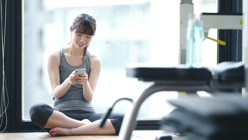 Young asian girl using a smart phone in fitness gym. | Shutterstock HD Video #1029804809