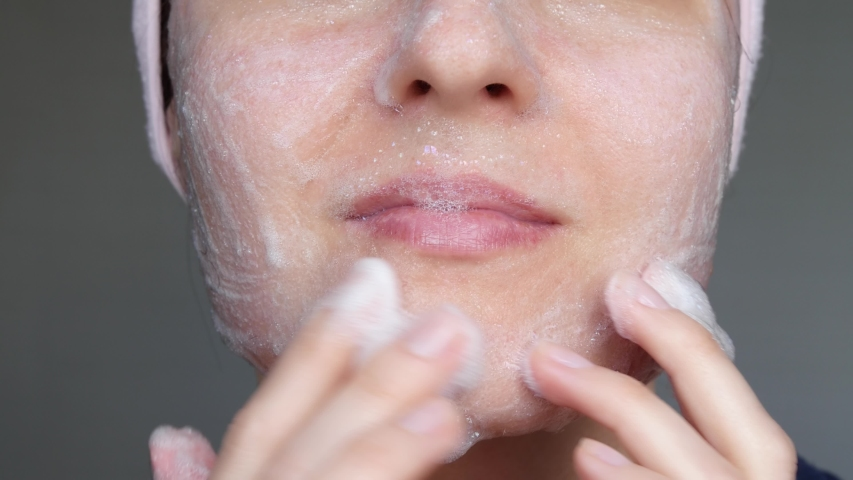Woman is apply a foaming means to cleanse the skin. Close-up of a woman's face. Soap bubbles on the skin. The concept of skin care and cleansing.   Shutterstock HD Video #1029837719