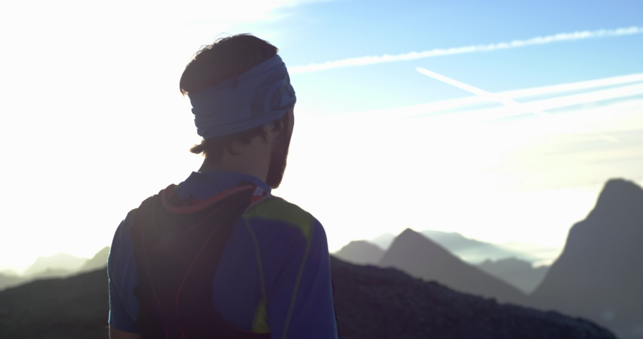 Trail runner man running reaching mountain top peak goal looking horizon view.Portrait shot.Wild nature outdoors at sunrise or sunset backlit.Training activity,sport,effort,challenge,willpower concept | Shutterstock HD Video #1029853529