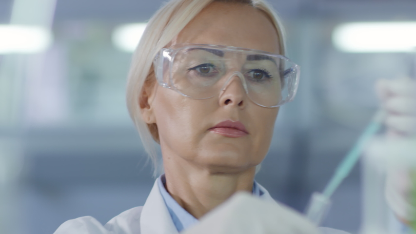Rack focused shot of female Caucasian scientist in medical uniform, gloves and goggles pouring blue liquid with pipette in test tube and then mixing it | Shutterstock HD Video #1029866549