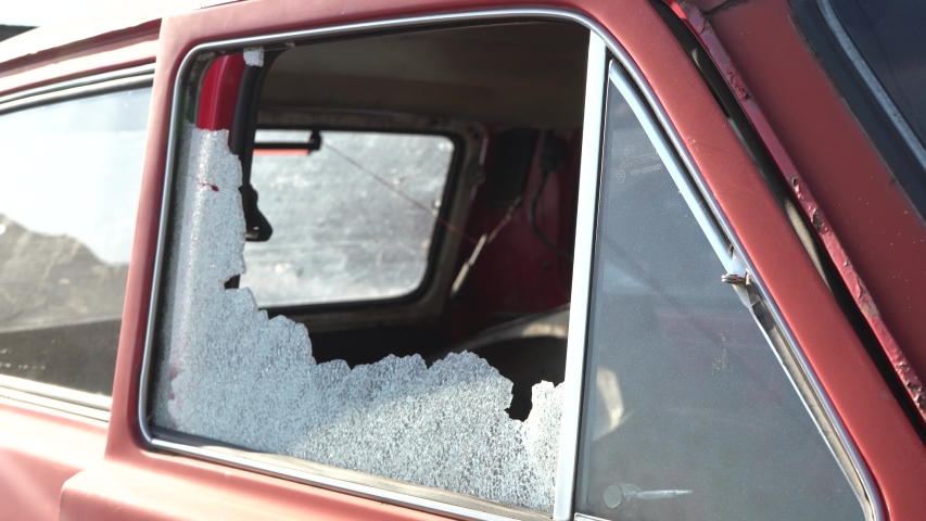 The car after the accident. Car window smashed by a thief. Car broken window. Broken right side window of a car parked on the street.