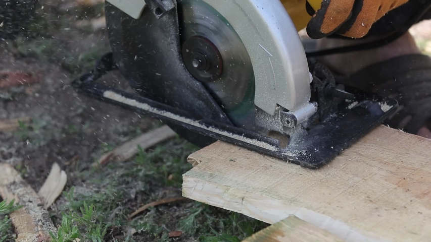 Building contractor worker using hand held worm drive circular saw to cut boards. Worker and the Woodworking. Full HD slow motion video, close up.