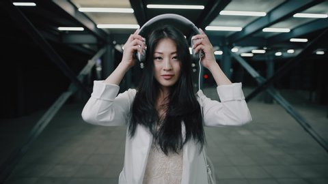 Asian woman puts on headphone walking at night underground