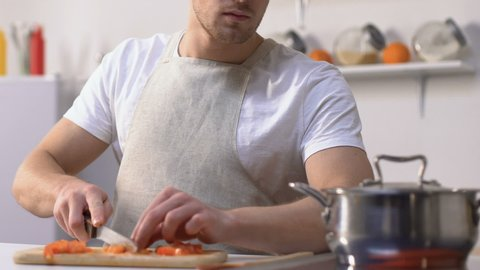 Man trying sauce in pan and screwing up face because of bad taste, cooking