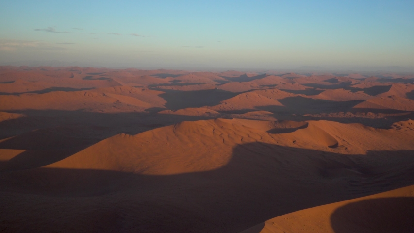 Wide Epic shot of Namibian Sossuvlei during Sunset with Nice Shadows and Orange Sand #1029919979