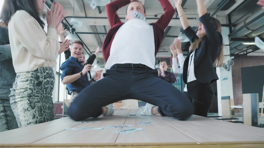 The manager dances on the table, scatters money, accelerates and slide on lap towards the camera. Colleagues celebrate success. Corporate party business team. Trendy office interior. Coworking