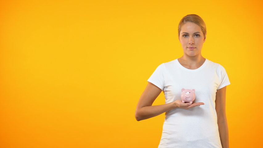Happy female covering piggybank by hand, safe bank deposit, account insurance   Shutterstock HD Video #1029942779