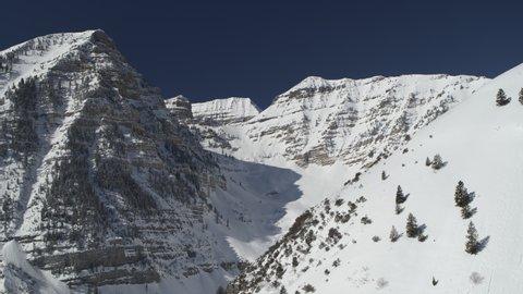 Aerial panning shot of snow covered mountain range / Aspen Grove, Utah, United States