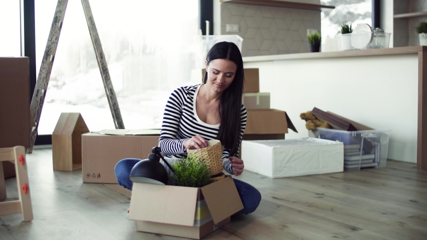 A young woman moving in new home, unpacking stuff. | Shutterstock HD Video #1030041539