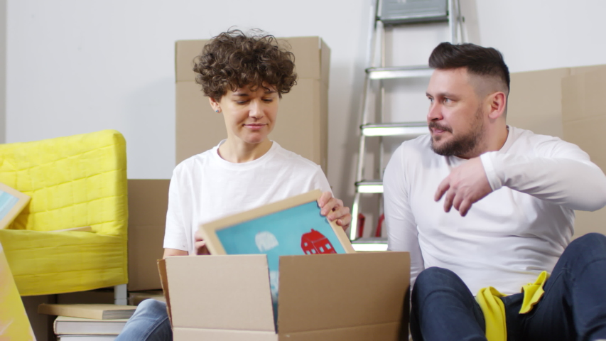 Panning thigh-up shot of cheerful Caucasian couple, having just moved in to new home, sitting on floor together and unpacking interior decorations, admiring framed pictures and photos and laughing   Shutterstock HD Video #1030095149