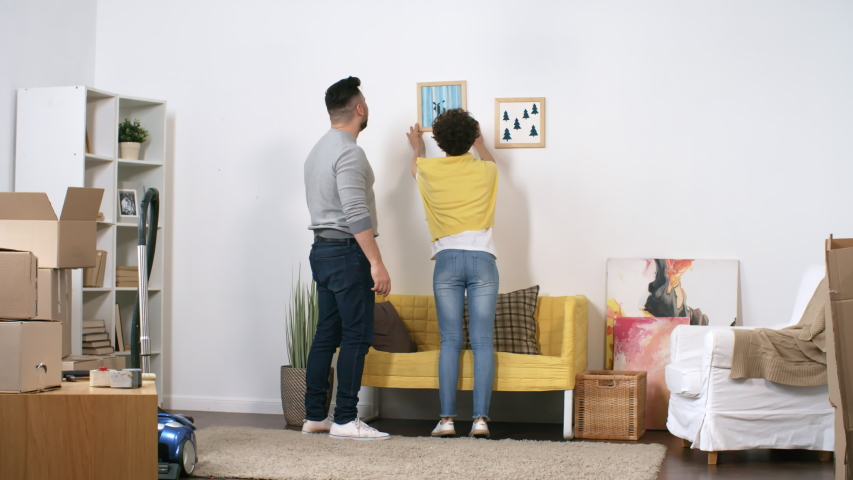 Full rear shot of affectionate Caucasian couple settling down in their new home and putting up framed pictures on wall together, adjusting and straightening them, then stepping back and embracing   Shutterstock HD Video #1030105499