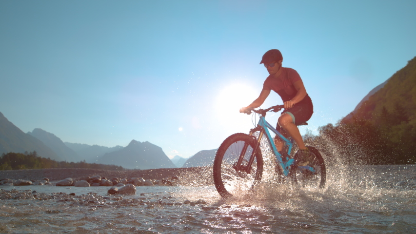 SUPER SLOW MOTION, LOW ANGLE: Fit man rides an e-bike in the shallow river and splashes water around him on a sunny summer day. Active male tourist rides a mountain bike in sunlit Soca river valley.
