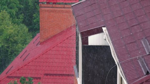 A heavy rain falls on the red metal roof of the house on a summer day. Slow motion