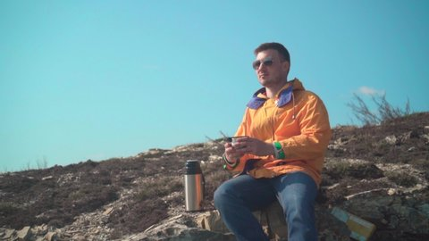 A young man in a yellow jacket, blue jeans and glasses sits in the mountains, enjoys the scenery and drinks tea from a thermos. In the background are hills and sky. Mountain landscape.