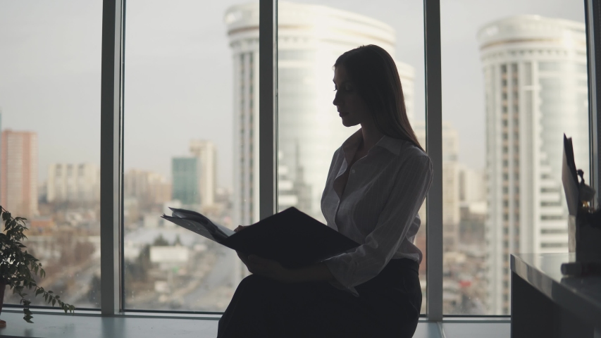 Silhouette of a woman working in the office. girl sits comfortably near the window and works with documents | Shutterstock HD Video #1030169279