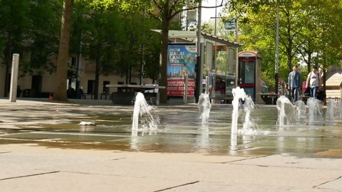 Belfast, Northern Ireland, UK - May 14, 2019: Fountains in Queen's Square with people walking