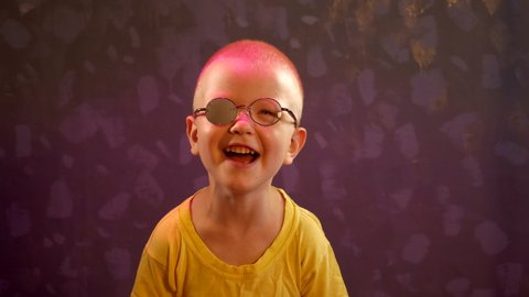 Portrait of funny child in new glasses with patch for correcting squint  Ortopad Boys Eye Patches nozzle for glasses for treatment of strabismus (lazy eye)