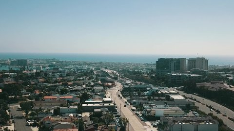 This is a drone shot above a small beach neighborhood in southern California. The drone shot is reasonably stagnant with busy roads and the Pacific ocean in the distance.