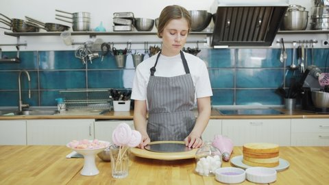 Tracking left shot of female pastry chef bringing freshly baked sponge cakes and thinking of future dessert at table in restaurant kitchen