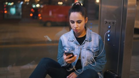 Young woman charging mobile phone, outdoors on bus train underground stop station, modern city while waiting bus transportation at night, energy electricity for devices