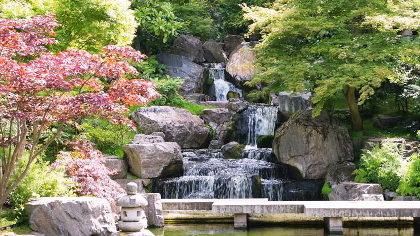 Waterfall with maple trees in Kyoto Japanese Garden in Holland Park green summer peaceful zen lake pond water and green trees in London, UK with nobody | Shutterstock HD Video #1030327439