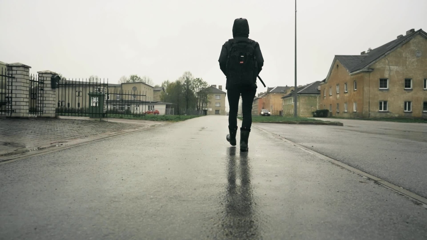 Girl walking in boots on wet ground at rainy day. Steadicam slow motion footage.  #1030391099