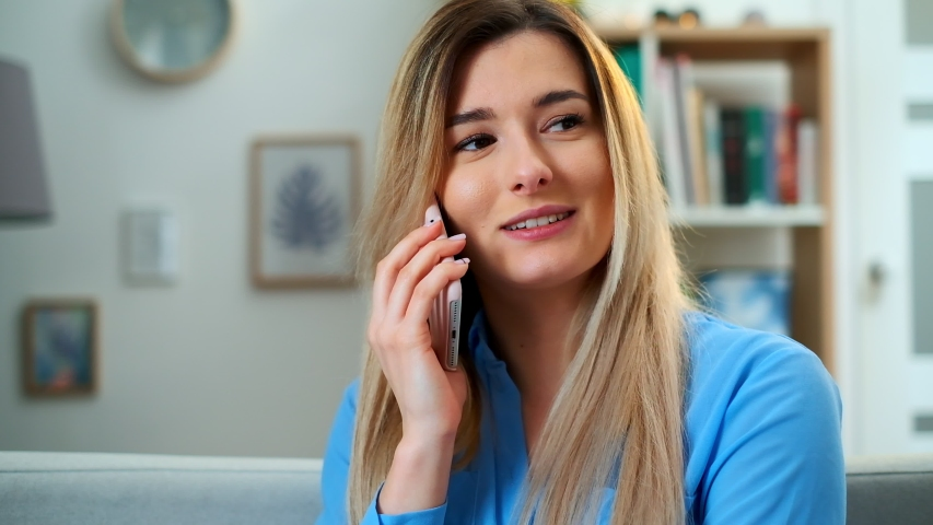 Close-up portrait of the attractive young woman talking on the phone cheerfully with a friend while sitting on the sofa in the living room. Indoors. | Shutterstock HD Video #1030402709